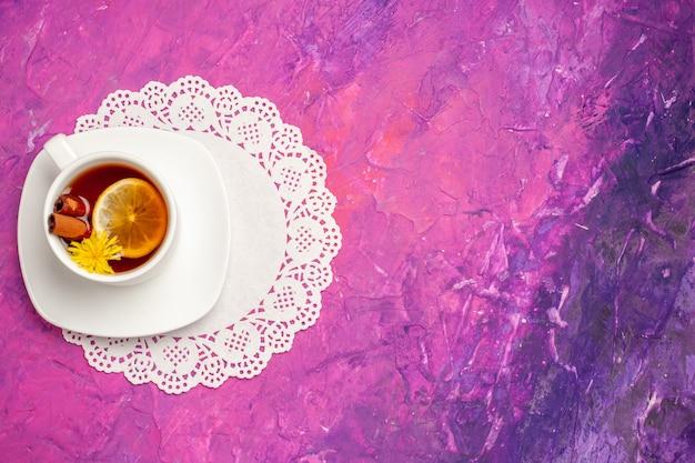 Bovenaanzicht kopje thee met citroen en kaneel op de roze tafel snoep kleur thee