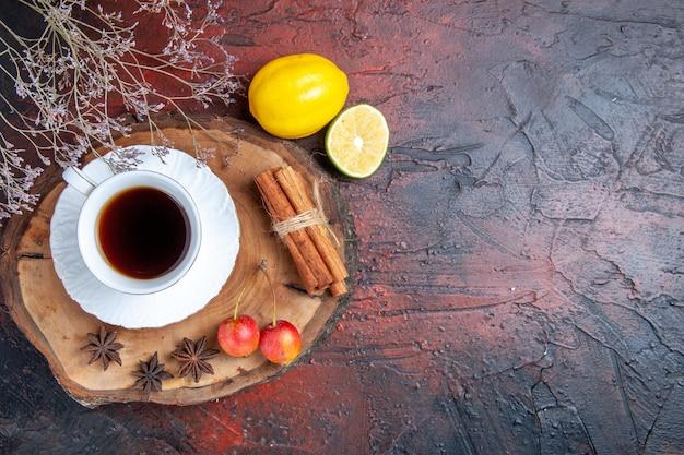 Bovenaanzicht kopje thee met citroen en kaneel op donkere ondergrond