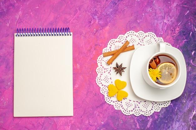 Bovenaanzicht kopje thee met citroen en kaneel op roze vloer thee kleur snoep
