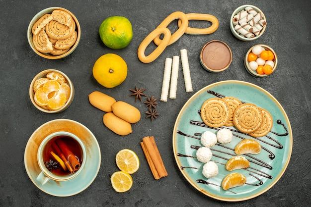 Bovenaanzicht kopje thee met citroen en koekjes op de donkere achtergrond