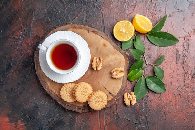 Bovenaanzicht kopje thee met citroen en koekjes op donkere tafel zoete koektaarten