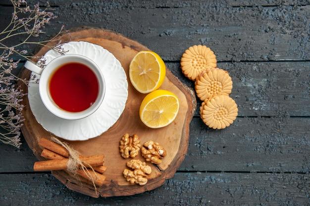 Bovenaanzicht kopje thee met citroen en koekjes op donkere tafel