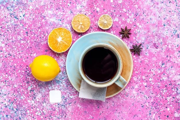 Bovenaanzicht kopje thee met citroen op het roze bureau.