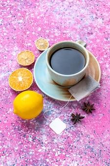 Bovenaanzicht kopje thee met citroen op roze achtergrond.