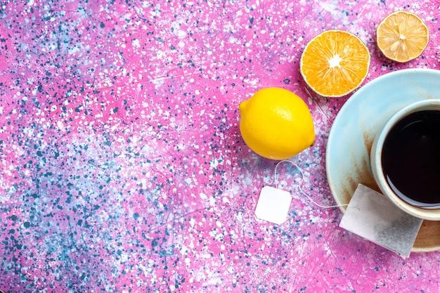 Bovenaanzicht kopje thee met citroen op roze bureau.