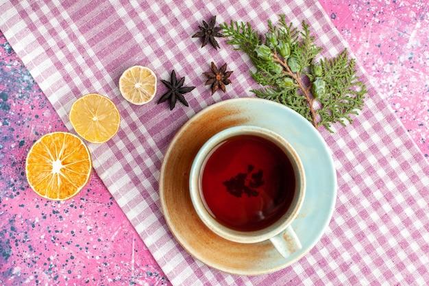 Bovenaanzicht kopje thee met citroen op roze bureau