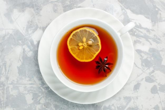Bovenaanzicht kopje thee met citroen op witte ondergrond