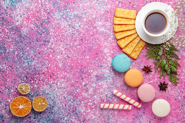 Bovenaanzicht kopje thee met crackers en franse macarons op het roze oppervlak