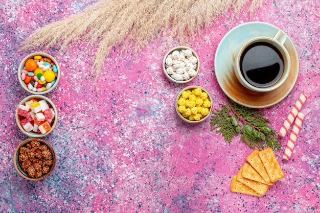 Bovenaanzicht kopje thee met crackers en snoepjes op het roze bureau