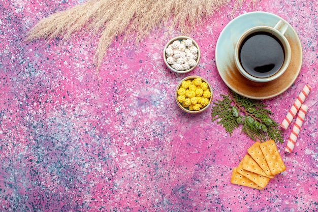 Bovenaanzicht kopje thee met crackers en snoepjes op roze oppervlak
