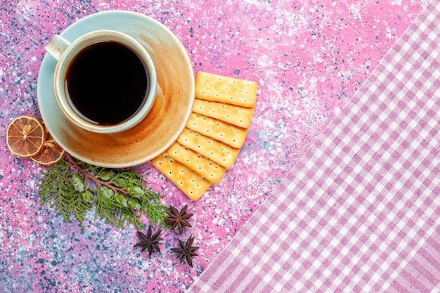Bovenaanzicht kopje thee met crackers op het roze bureau