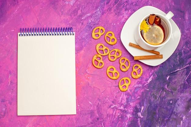 Bovenaanzicht kopje thee met crackers op lichtroze tafelkleur citroen snoep thee