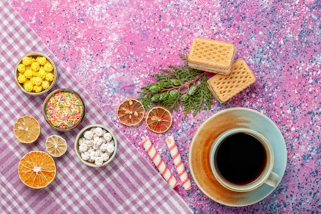 Bovenaanzicht kopje thee met crackers wafels en snoepjes op roze bureau