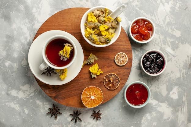 Bovenaanzicht kopje thee met dessert en verschillende jam op witte backgruond fruit jam thee zoete suiker