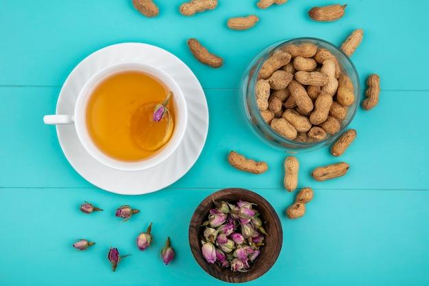 Bovenaanzicht kopje thee met een schijfje citroen en pinda's op een lichtblauwe achtergrond