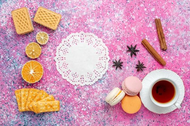 Bovenaanzicht kopje thee met franse macarons en crackers op het roze bureau