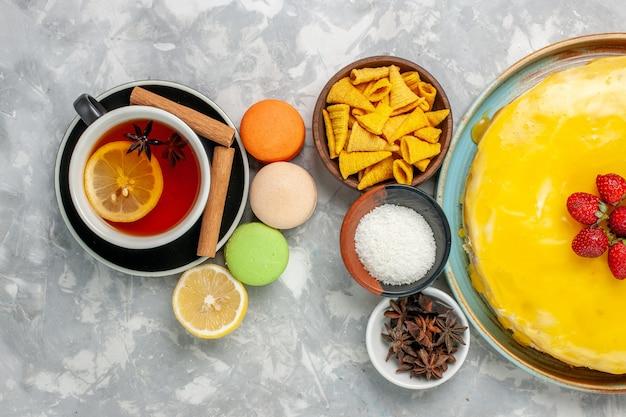 Bovenaanzicht kopje thee met franse macarons en heerlijke gele stroopcake op witte ondergrond
