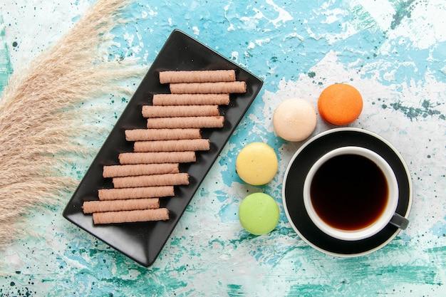 Bovenaanzicht kopje thee met franse macarons en koekjes op blauwe ondergrond