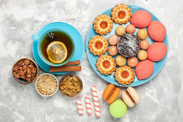 Bovenaanzicht kopje thee met franse macarons koekjes en gebak op witte ondergrond