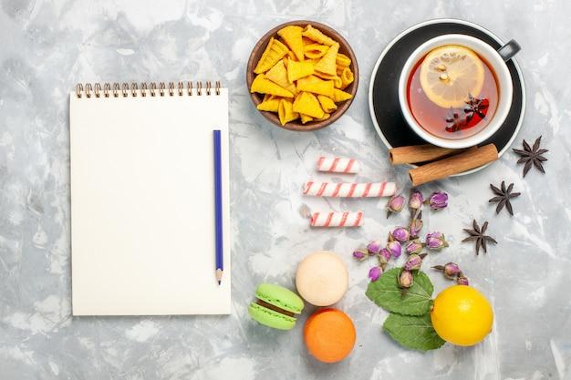 Bovenaanzicht kopje thee met franse macarons op licht-wit bureau