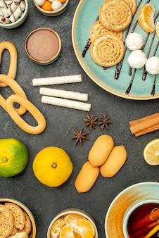 Bovenaanzicht kopje thee met fruit en koekjes op de donkere achtergrond