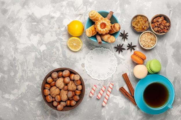Bovenaanzicht kopje thee met gebak en noten op witte ondergrond