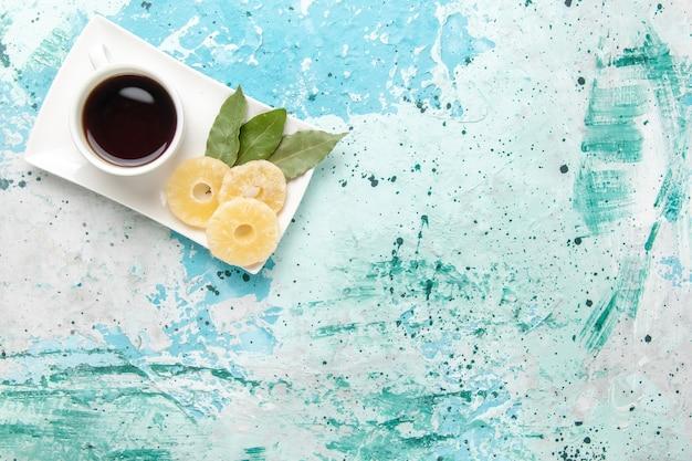 Bovenaanzicht kopje thee met gedroogde ananasringen op lichtblauw oppervlak
