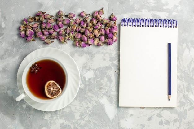 Bovenaanzicht kopje thee met gedroogde bloemetjes en blocnote op het lichtwitte bureau
