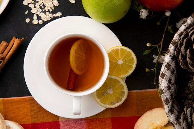 Bovenaanzicht kopje thee met gesneden citroen en kaneel met appels op tafel