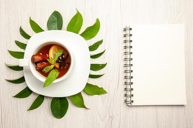 Bovenaanzicht kopje thee met groene bladeren op witte bureau kleur thee fruit ceremonie