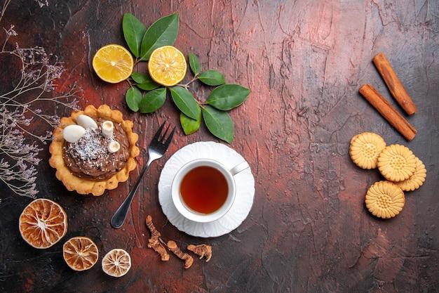 Bovenaanzicht kopje thee met heerlijke kleine cake op donkere tafel, koekje dessert