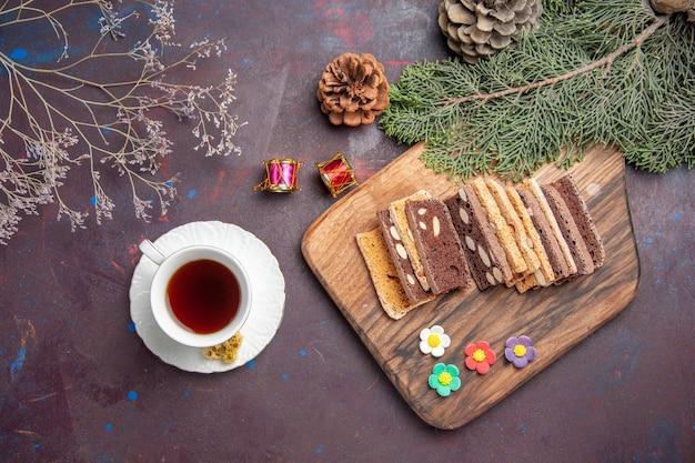 Bovenaanzicht kopje thee met heerlijke plakjes cake op een donkere ruimte