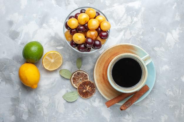 Bovenaanzicht kopje thee met kaneel citroen en kersen op het witte oppervlak drinken thee kaneel citroen kleur