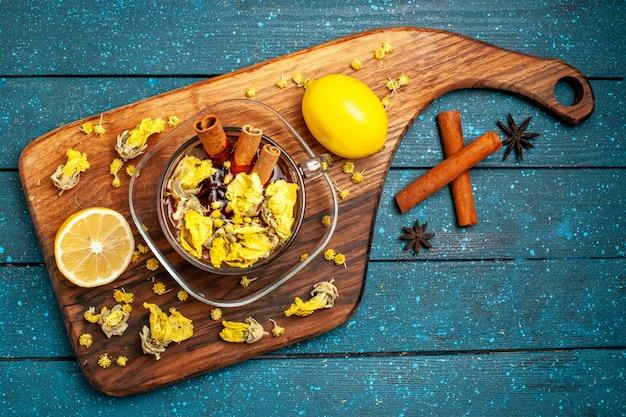 Bovenaanzicht kopje thee met kaneel en citroen op blauw bureau