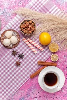 Bovenaanzicht kopje thee met kaneel en citroen op de roze