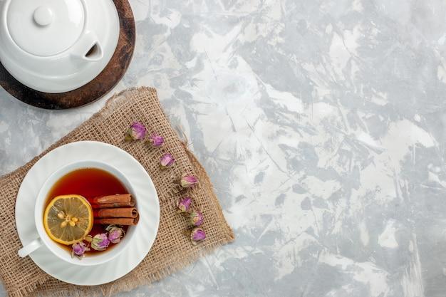 Bovenaanzicht kopje thee met kaneel en citroen op het lichtwitte oppervlak