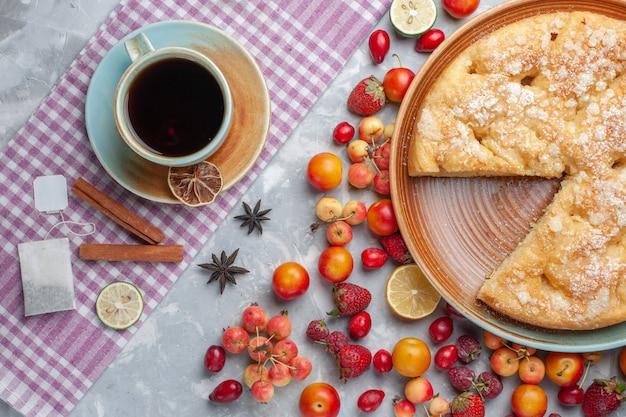 Bovenaanzicht kopje thee met kaneel en fruit taart op het licht bureau thee drinken warm ontbijt
