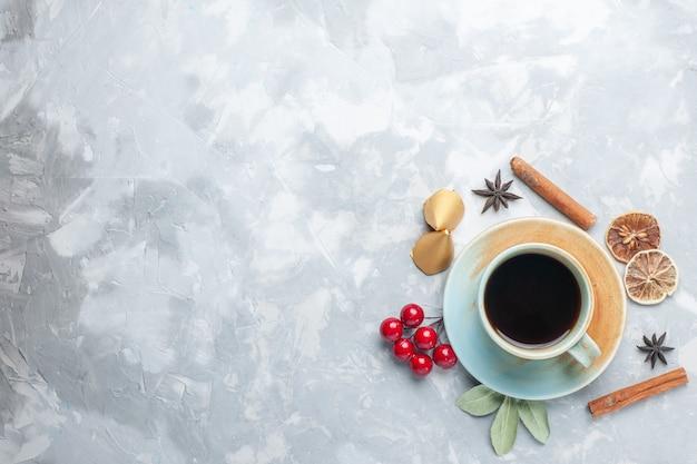 Bovenaanzicht kopje thee met kaneel en gedroogde citroen op het witte bureau thee snoep kleur ontbijt