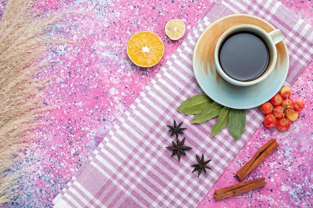 Bovenaanzicht kopje thee met kaneel en kersen op lichtroze backgruond thee drinken fruitkleur