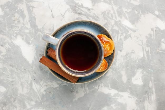 Bovenaanzicht kopje thee met kaneel en kleine cakes op witte ondergrond