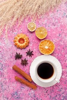 Bovenaanzicht kopje thee met kaneel en koekjes op roze desk cookie koekje suiker zoet