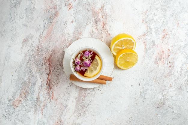 Bovenaanzicht kopje thee met kaneel en plakjes citroen op witruimte