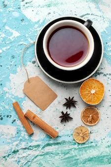 Bovenaanzicht kopje thee met kaneel op blauwe ondergrond