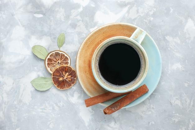 Bovenaanzicht kopje thee met kaneel op het witte oppervlak drinken thee kaneel citroen kleur