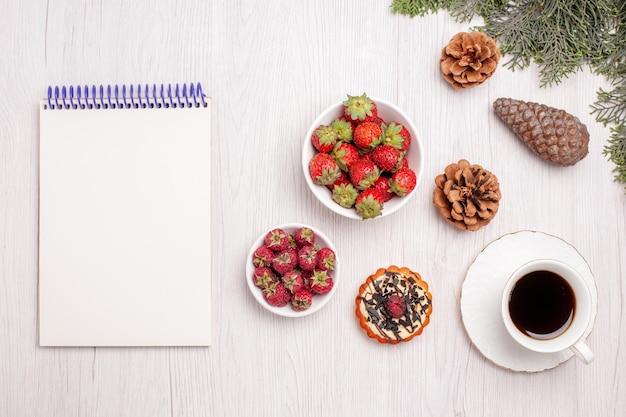 Bovenaanzicht kopje thee met kleine cake en fruit op wit bureau fruit thee berry cookie cake