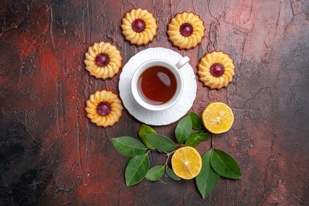Bovenaanzicht kopje thee met kleine koekjes op donkere tafel koekje zoete dessert