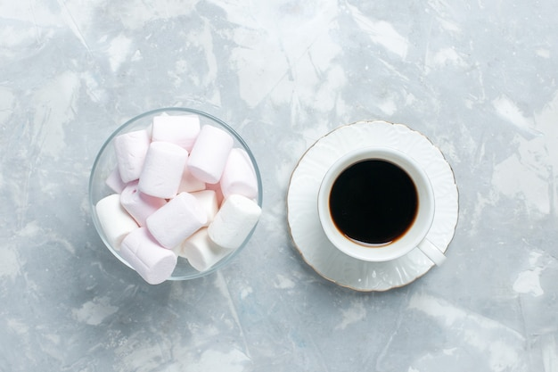 Bovenaanzicht kopje thee met kleine marshmallows op lichtwit bureau.