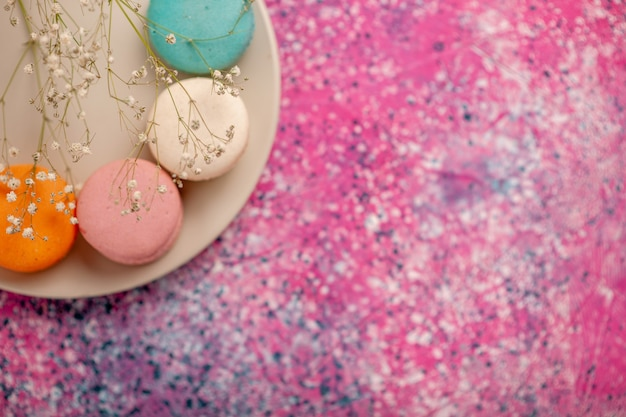 Bovenaanzicht kopje thee met kleurrijke franse macarons op roze bureau