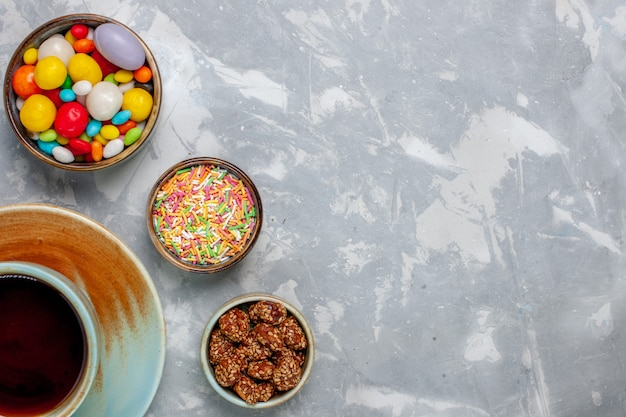 Bovenaanzicht kopje thee met kleurrijke snoepjes op licht-wit bureau candy bonbon goodie sugar pie sweet
