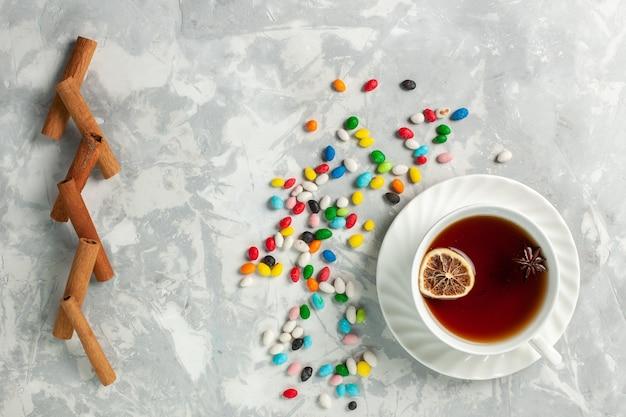 Bovenaanzicht kopje thee met kleurrijke verschillende snoepjes en kaneel op licht-wit bureau